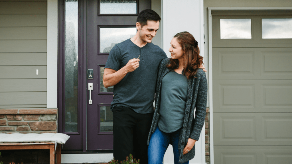 man and woman in front of house, millennials delaying buying a house due to debt