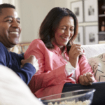 couple sitting on couch shopping online for life insurance