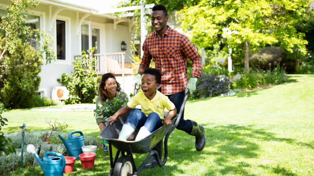 dad and two kids playing in yard, protected with mortgage insurance