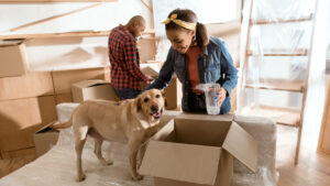 woman with her dog unpacking new home protected with term life insurance policy