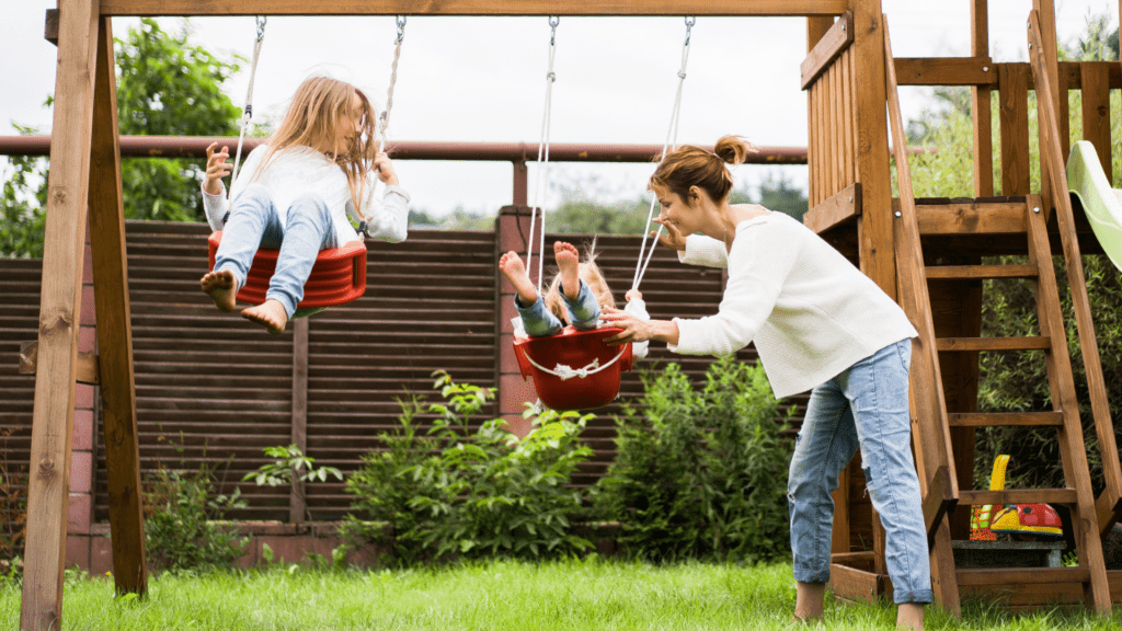 mom and two kids playing on swingset, protected with term life insurance